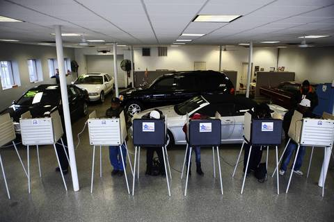 Voters fill out their ballots at Sam's Auto Sales, 6815 S. Western Ave., Chicago.
