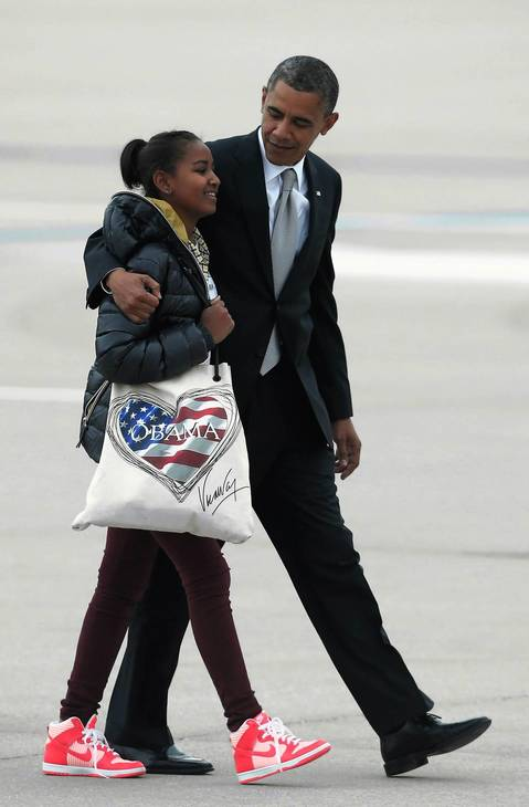 President Barack Obama walks with his daughter Sasha across the tarmac from Marine One to Air Force One at O'Hare International Airport as the Obama family leaves Chicago to return to Washington, DC.