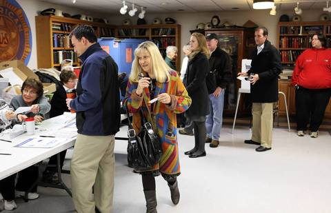 Karen Kelly maneuvers to the next available election judge before voting at the American Legion Post 80 in Downers Grove.