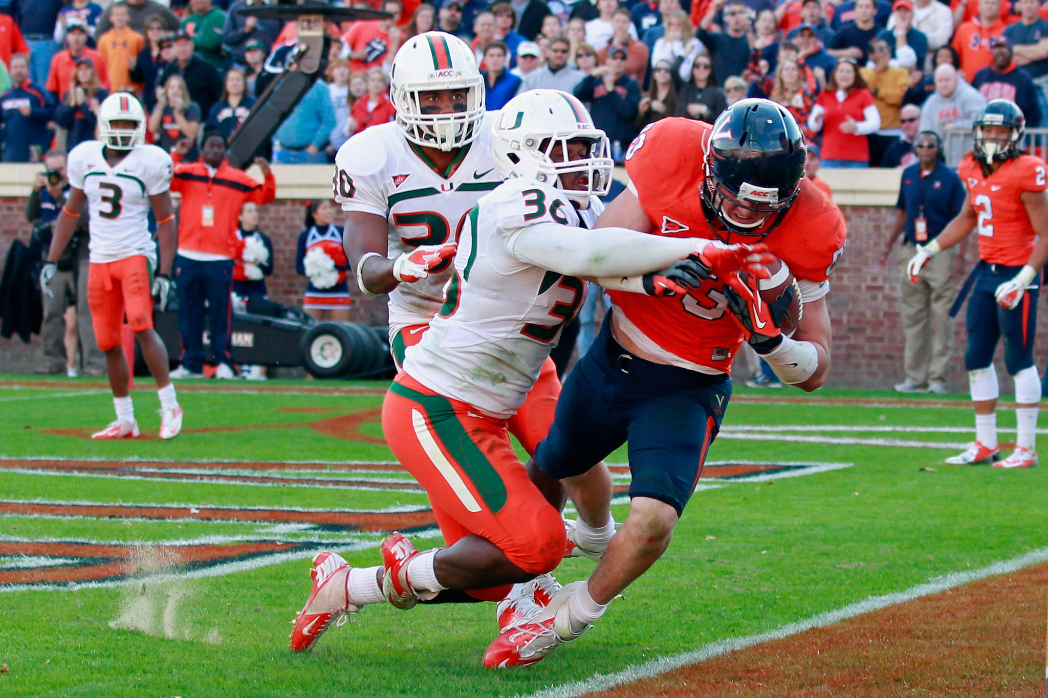 Tight end Jake McGee #83 of the Virginia Cavaliers catches the ball for the game-winning touchdown in the final seconds as linebacker Gionni Paul #36 of the Miami Hurricanes defends