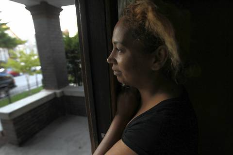 Maria Figueroa watches as daughter Yajaira boards a school bus outside their Chicago home.