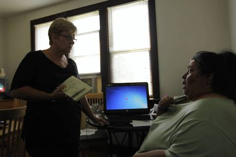Outreach worker Martha Small talks to Alex's mother, Carmen Frausto, during a home visit in LaSalle.