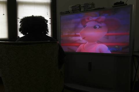 While truant from school, Alex Frausto plays a video game as his niece watches cartoons.