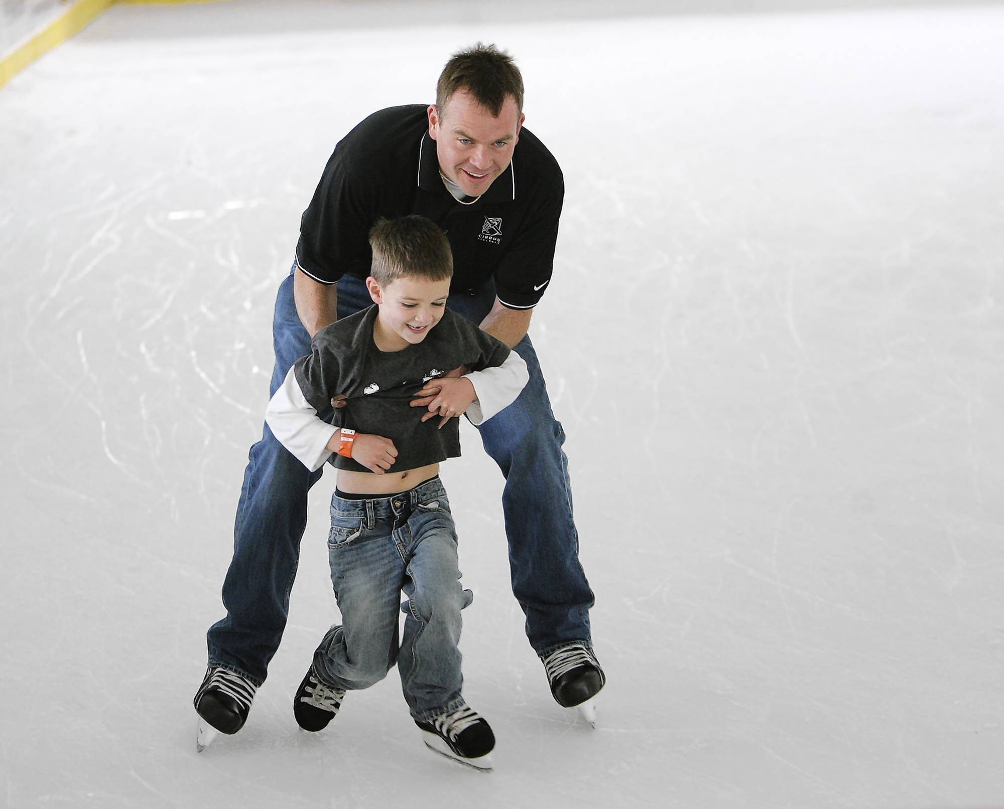 Brad Pierce teaches his son Hunter, 5, how to skate on Sunday, November 28, 2010, at Winter Park's Central Park. Children and adults enjoyed the ice while the temperature outside climbed into the 80's. The holiday ice rink will be open until Jan. 9.