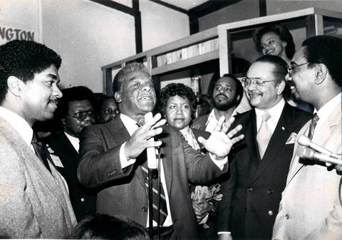 Mayor Harold Washington speaks at Catfish Digby's restaurant before a second fundraising gathering of Cook County Democrats. Washington is flanked by (from left) Ald. Timothy Evans (4th), fiancee Mary Ella Smith, Ald. Clifford Kelley (20th) and Ald. Bobby Rush (2nd).