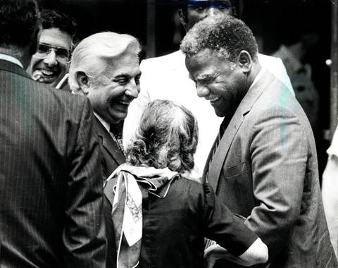 Mayor Harold Washington stands outside City Hall in the afternoon, yucking it up with Ald. Roman Puckiski, Ald. Larry Bloom and a passerby.