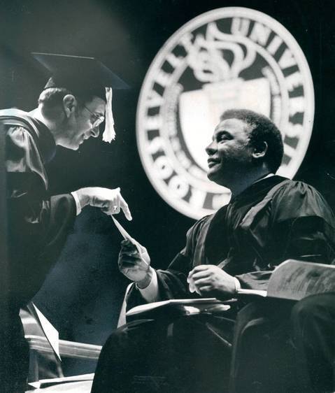 "Having received his diploma, a Roosevelt University graduate stops on the stage for a brief word with featured speaker Mayor Harold Washington during commencement exercises at the Auditorium Theater. Washington, a member of the class of 1949, told the 550 graduates that ""by the year 2000, Chicago will be populated by approximately equal numbers of blacks, whites, and Hispanics and an equal number of Asians."""