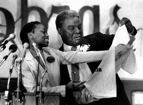 "Samantha Whitside, student council president at Collins High School, presents a school T-shirt to Mayor Harold Washington, who appeared at the school for a Black History Month address. The shirt is emblazoned with the words ""Living the Dream"" and shows a city landscape with Mayor Washington and the Rev. Martin Luther King Jr. rising from it."