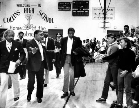 "Mayor Harold Washington gestures in apology to a student seeking a handshake as he is accompanied by Principal Grady Jordan across the Collins High School gym. ""You must be heard to be considered,"" he told an enthusiastic audience. ""You must register and vote but that is just the start..."""