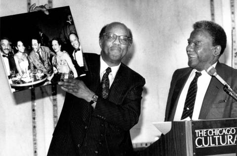 Historian Dempsey Travis presents a historic photograph to Mayor Harold Washington during a Celebration of the History of Black Jazz at the Chicago Public Library Cultural Center. In the picture, along with a young Washington, left, are Duke Ellington, center, and Travis.