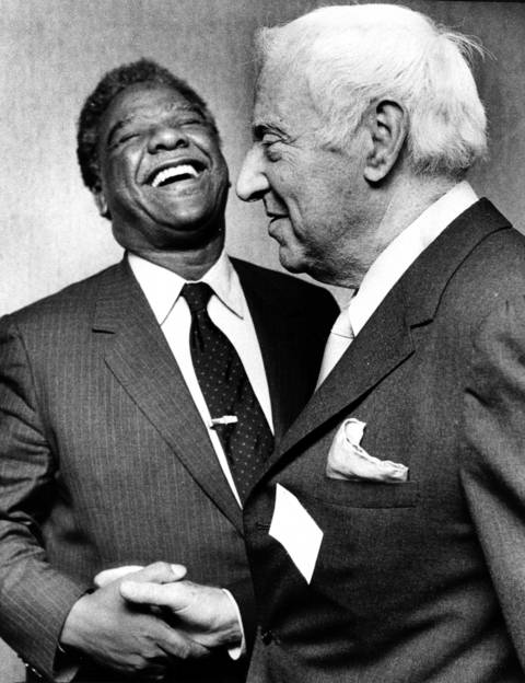 """Mayor Washington and former city treasurer Marshall Korshak share a joke in the Palmer House hotel. Washington, addressing a meeting of the Executives' Club of Chicago, urged the two City Council factions to """"come together."""""""