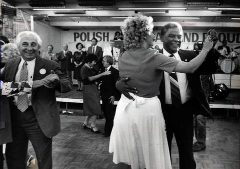 "After warring over control of city contracts, political rivals Ald. Roman Pucinski and Mayor Harold Washington ""cut the rug"" at the Taste of Polonia. Washington's partner is Delores Gentile of the Copernicus Foundation."
