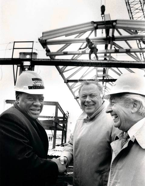 Mayor Harold Washington and Ald. Roman Pucinski flank United Airlines President James Hartigan as the last of 27 130-foot steel trusses is erected at the site of the carrier's new terminal at O'Hare International Airport.