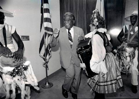 Mayor Harold Washington tries a polka step while Vlasta, representing Czechoslovakia, plays the accordian in the Mayor's outer office. Vlasta gets a little help from Thunder Sky Drummers Abdul Sabur, left, and Prince Ravanna Bay. The participants are appearing at the 1985 International Folk Fair.