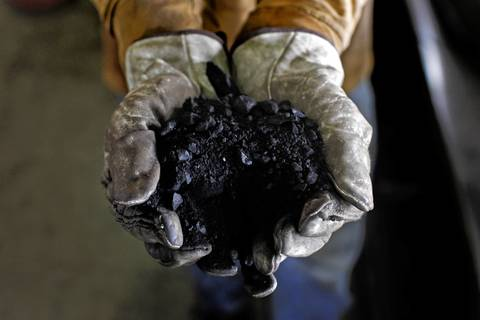 An operator holds some coal in his hands at the Midwest Generation's Fisk Generating Station as they worked on cleaning coal built up on the coal bunkers one day before its closing.