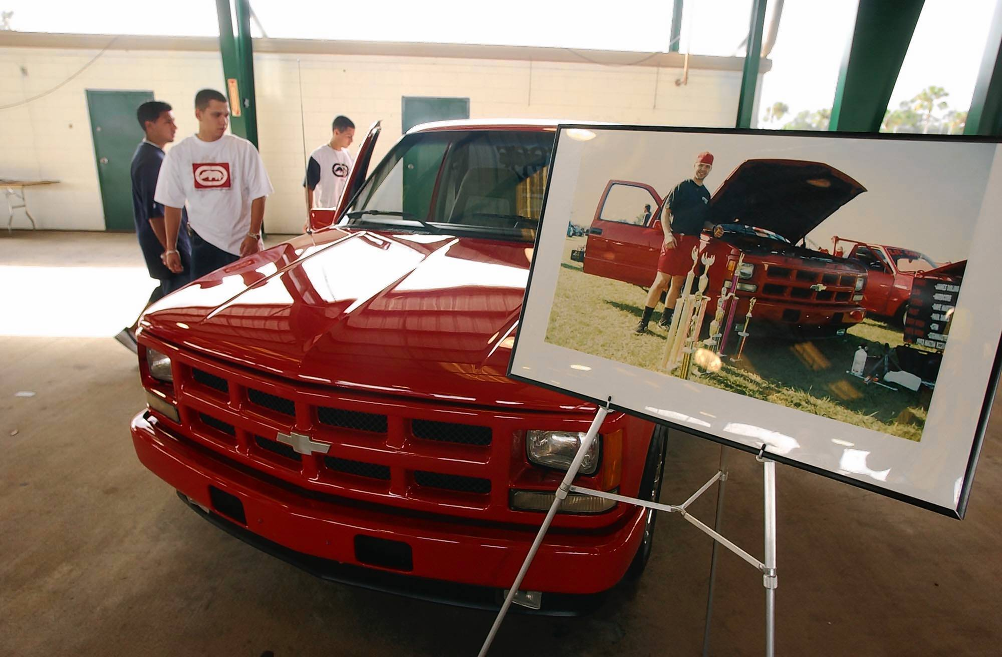 A photo of Larry Neal Oliver Jr., 22, is displayed in front of his customized red pickup at the 2004 Larry Neal Oliver Jr. Memorial Show. The 2012 show on Saturday will be the last, organizers say. Oliver was shot to death in November 1995 by a man who wanted to steal the 1993 Chevrolet Stepsider that Oliver worked two jobs to care for.