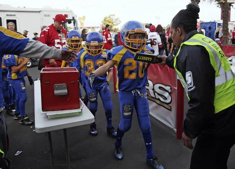Youth football players go through a security check at Candlestick Park.