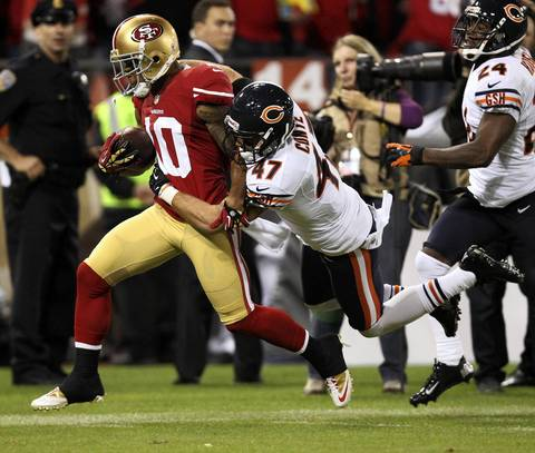 49ers wide receiver Kyle Williams gains yardage on a long pass as Chris Conte defends in the first quarter.