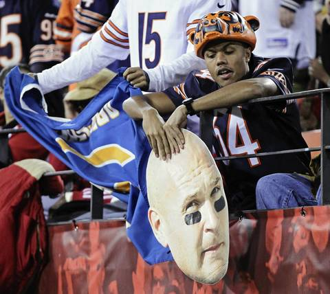 A Bears fan holding a cutout of Brian Urlacher's face sits down after a 49ers touchdown in the first quarter.