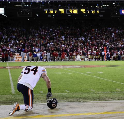 Brian Urlacher kneels with his head lowered in the fourth quarter.
