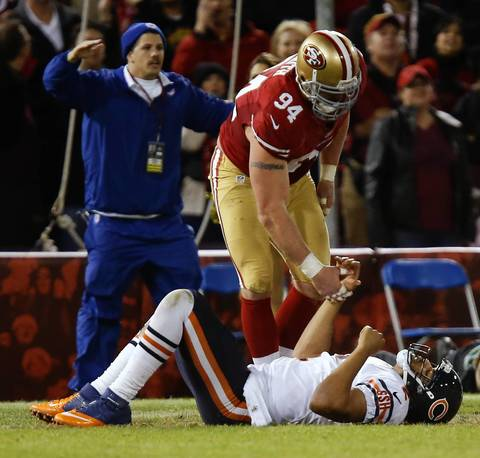 Bears quarterback Jason Campbell is helped up off the grass by 49ers defensive end Justin Smith after Campbell fumbles the ball in the fourth quarter. The ruling was a safety on the play.