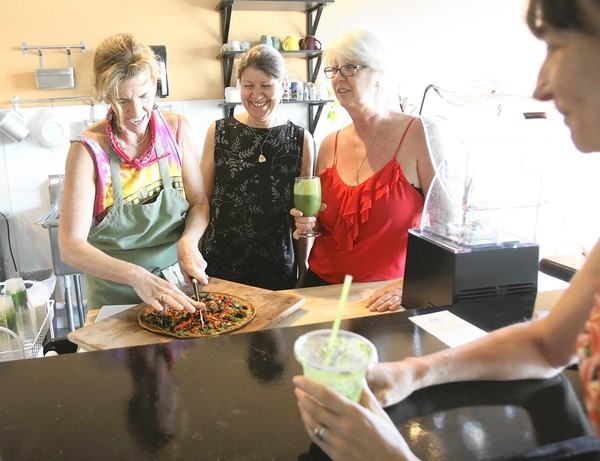 Bridgette Stringfellow, left, prepares a raw, organic pizza as owners of Living Green Health  Foods, Nina Reigger and Michelle Kristof watch .  (Tom Benitez/Orlando Sentinel)