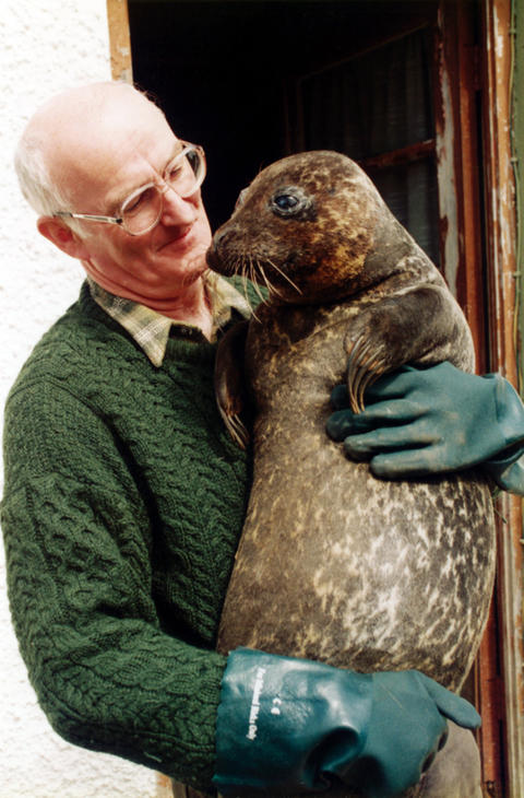 Frank Mulreany holds Sally the seal in Dungloe, Ireland.