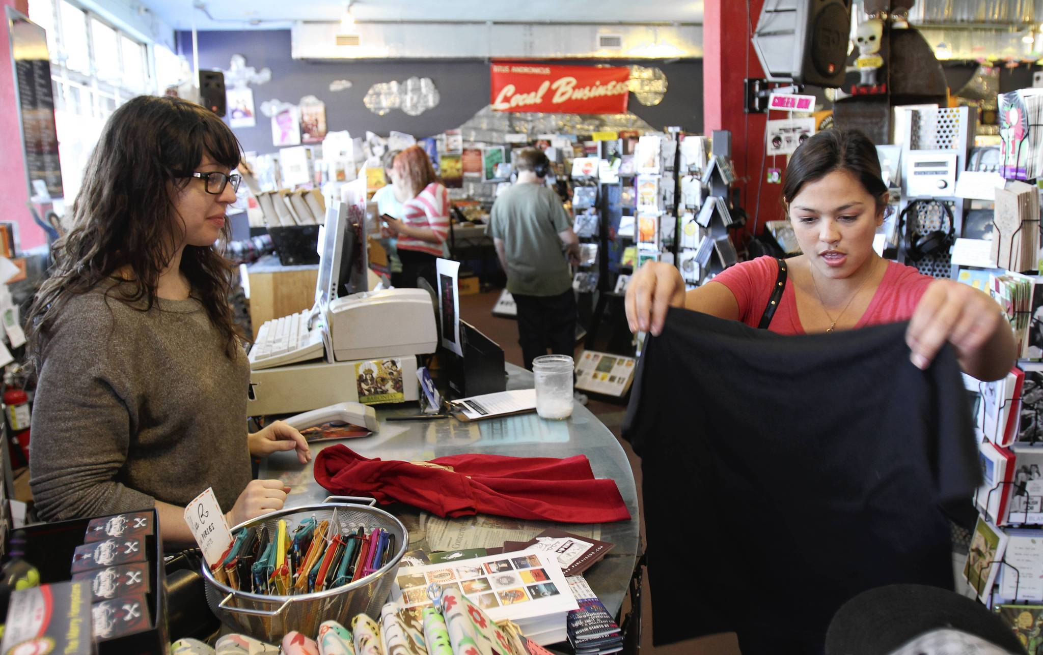 Heather Frechette, right, buys T-shirts from Tierney Tough at Park Avenue Compact Discs in Orlando's Audubon Park neighborhood Saturday.
