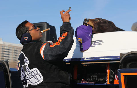 Sal Khan takes a photo of a bear's head with a Vikings cap in its mouth, while tailgating before the start of the Chicago Bears game against the Minnesota Vikings at Soldier Field in Chicago on Sunday.