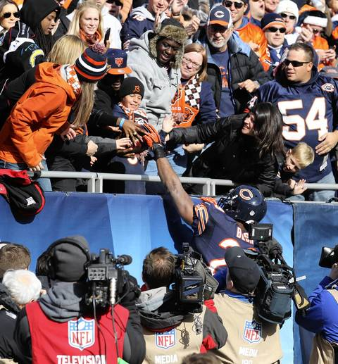 Running back Michael Bush hands his touchdown ball to a fan on the north end zone during the first half.