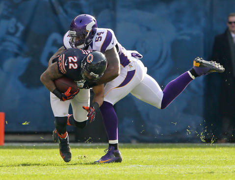 Running back Matt Forte is tackled by Vikings middle linebacker Jasper Brinkley during the first half.