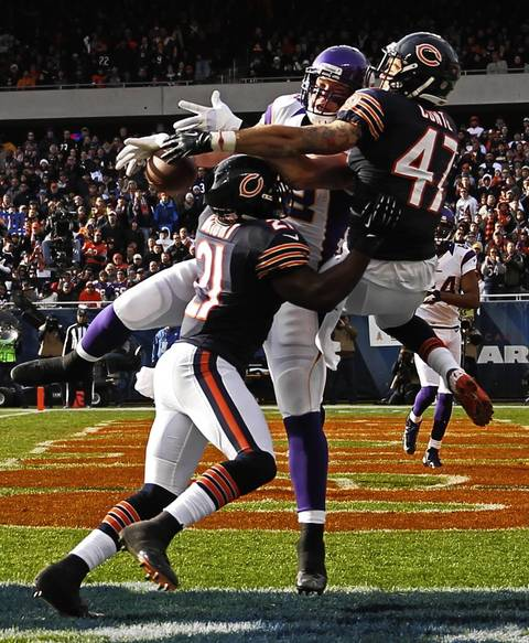 Chris Conte and Major Wright break up pass intended for the Vikings' Kyle Rudolph during the 2nd quarter.