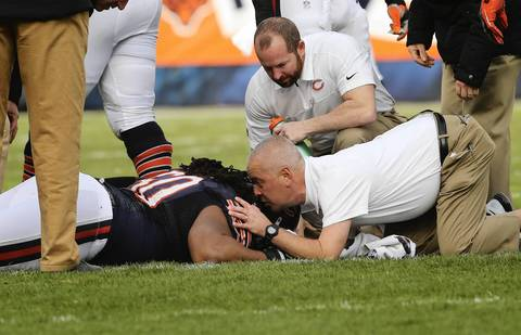 Bears guard Lance Louis is looked after following a hit during the second half.