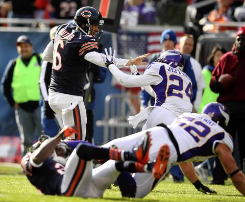 Jay Cutler stiff arms the Vikings' A.J. Jefferson as Devin Hester is injured during the 1st quarter.