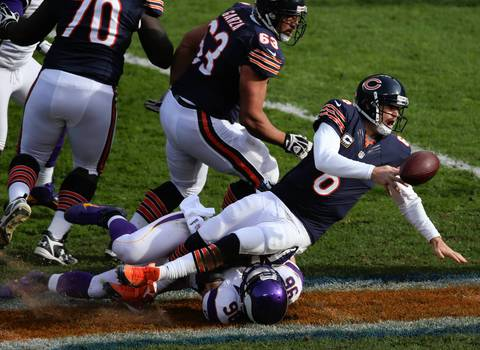 Jay Cutler shovels the ball away before being brought down by the Vikings' Brian Robison in the 2nd quarter.