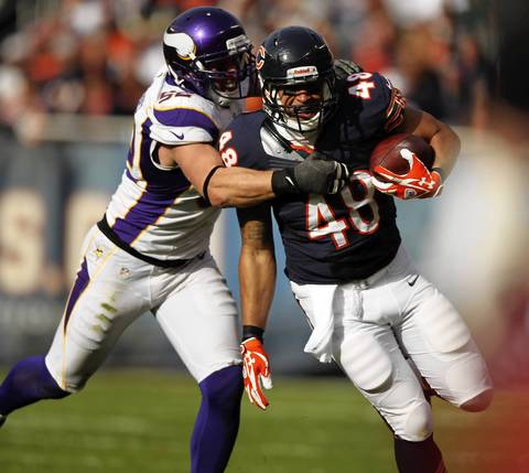 Tight end Evan Rodriguez runs after a catch as the Vikings' Chad Greenway holds on during the 2nd quarter.