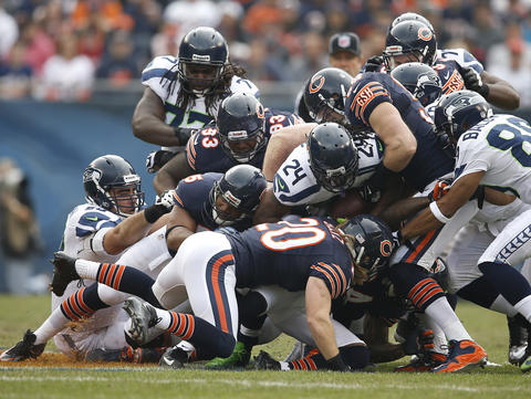 Seahawks running back Marshawn Lynch is tackled by Brian Urlacher and other defenders and fumbles the ball in the first quarter.