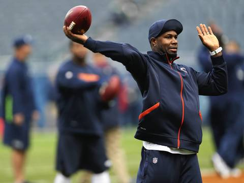 Injured Devin Hester warms up before the start of the game.
