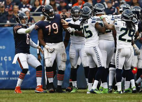 Jay Cutler pulls tackle Jonathan Scott (79) from fighting with Seahawks defensive tackle Alan Branch (99) in the third quarter.