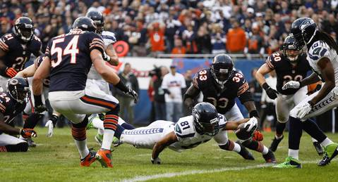 Seahawks wide receiver Golden Tate dives across the goal line in front of Charles Tillman to score the then-go-ahead touchdown in the final minute of play of the fourth quarter.
