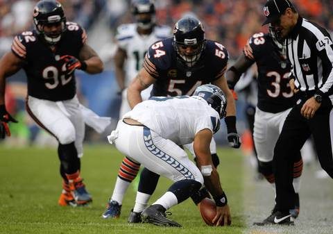 Seahawks quarterback Russell Wilson picks up a fumble that Charles Tillman forced along the sideline in the fourth quarter.