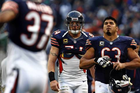 Brian Urlacher and Roberto Garza walk off the field following a 23-17 loss in overtime.