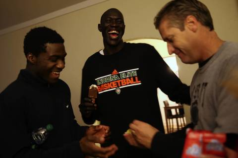 Mooseheart basketball team members Kevin Gbadebo, left, and Makur Puou, center, joke with coach Ron Ahrens as the squad has a movie night at the coach's house.