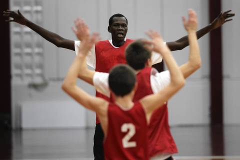 Mooseheart boys' basketball player Akim Nyang leads a warm up during practice on November 15, 2012.