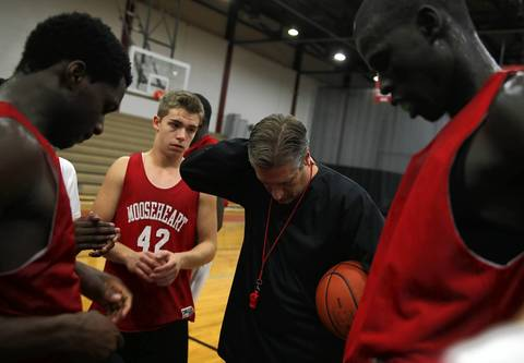 """Everyone pray tonight,"" said Mooseheart head basketball coach Ron Ahrens as he addressed Mangisto Deng, right, and the rest of his team after practice on December 3, 2012. Deng and his Sudanese teammates Akim Nyang and Makur Puou were declared ineligible by the IHSA and their short term fate will be determined in a Kane County courtroom Tuesday morning."