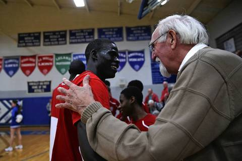 Bill Roberts, who played with the Boston Celtics in 1948-49, greets Mooseheart's Mangisto Deng before the team's 58-51 loss to Hinckley-Big Rock in Hinckley, Ill. Roberts, who lives in DeKalb, called coach Ron Ahrens to give his moral support and Ahrens invited Roberts to join the team on the bench for the game.
