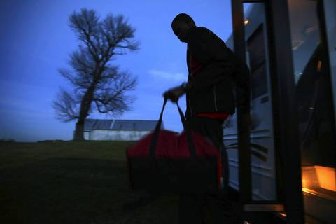Mooseheart's Akim Nyang is the first to exit the team bus at Hinckley-Big Rock High School in Hinckley, Ill. Mooseheart would go on to lose 58-51.