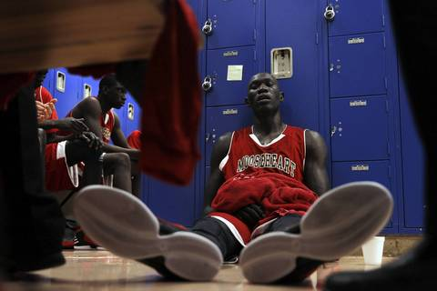 Mooseheart's Makur Puou, who would score 25 points, sits on the locker room floor during halftime of 58-51 loss to Hinckley-Big Rock in Hinckley, Ill.