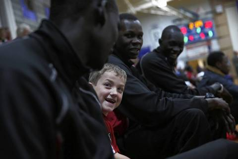 Mooseheart head coach Ron Ahrens' son Turner, 7, sits with Mangisto Deng (left), Akim Nyang and Makur Puou (right) during junior varsity game at Hinckley-Big Rock High School in Hinckley, Ill.