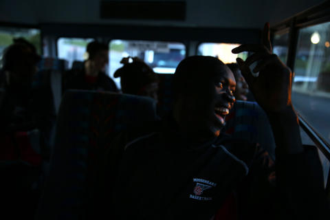 Mooseheart's Makur Puou smiles while getting encouragement as the team bus leaves campus to head to Hinckley-Big Rock High School in Hinckley, Ill.